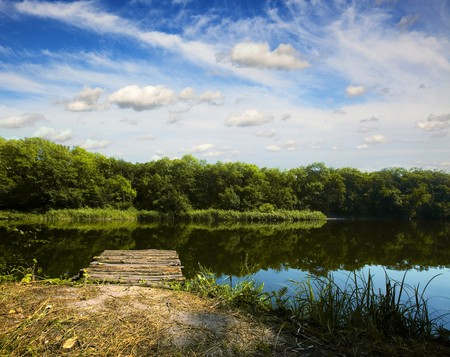Wooden pier on summer river and forest on the backside photo