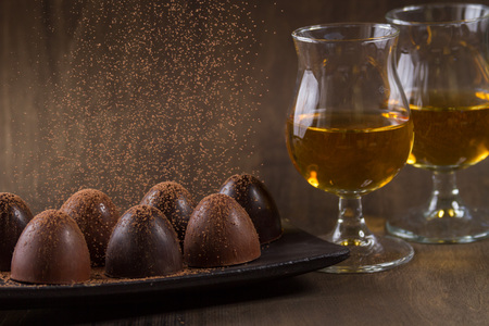 brandy: glass of brandy with chocolate on wooden table