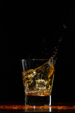 Whiskey glass on black wood surface