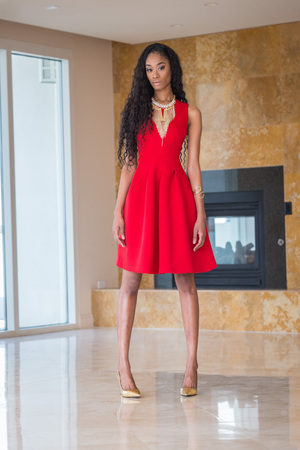 woman red dress: Portrait of a beautiful young black woman in red dress fashion outfit Stock Photo