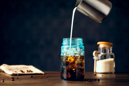 Milk Pouring Into Iced Organic Coffee Served In Blue Mason Jar On Table With Natural Sugar. Copy Space With Selective Focus. Stock Photo