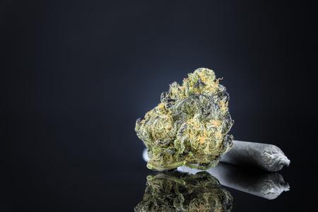 Schließen Sie herauf Makro der Marihuana-Knospe mit Verbindung auf dunklem schwarzem Tabellen-Hintergrund. Selektiver Fokus mit Kopien-Raum.