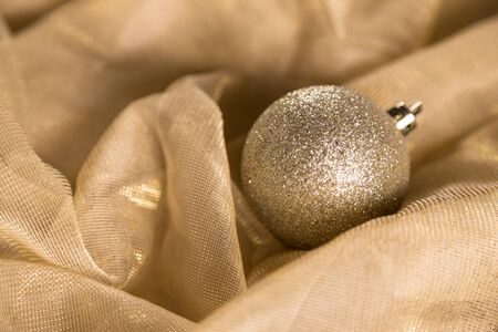 Closeup Warm Gold Glitter Sparkle Christmas Bauble On Shiny Fabric Background. Selective Focus With Copy Space.
