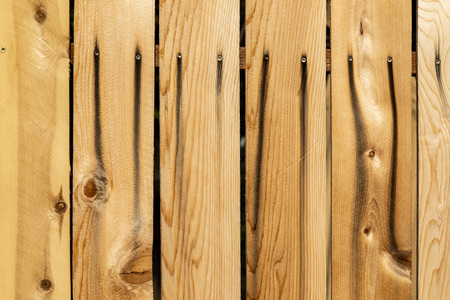 Close up weathered brown wood background surface. New wooden wall texture planks with knots.