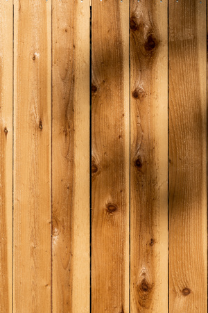 Vertical weathered brown wood background surface. Wooden wall texture rustic planks with knots. Imagens