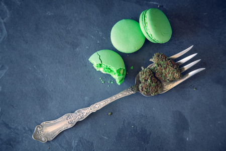 Green Marijuana Edibles On Fork With Cannabis Buds On Dark Slate Background. Top View Selective Focus With Copy Space.