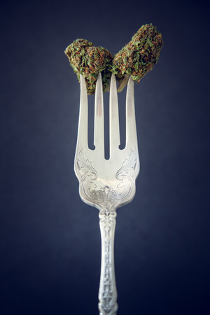 Vertical Marijuana Buds Close Up On A Vintage Silver Fork On Low Key Dark Background. Selective Focus With Copy Space. Imagens