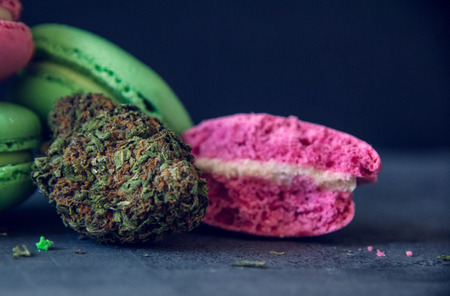 Close Up Marijuana Edibles With Cannabis Nugs On Dark Slate Background. Selective Focus With Copy Space.