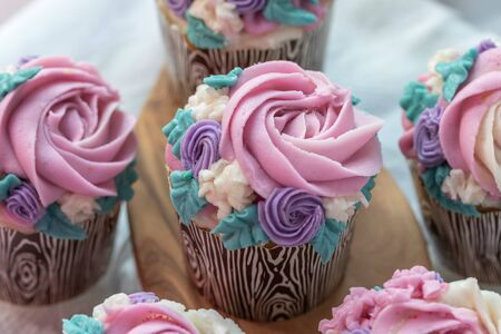 Close up Floral cupcakes on wood background with copy space