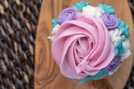 Top Down Floral cupcakes on wood background with copy space