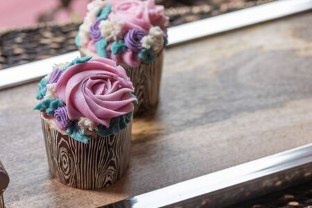Floral cupcakes on wood background with copy space