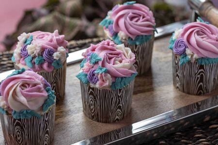 Floral cupcakes on wood background