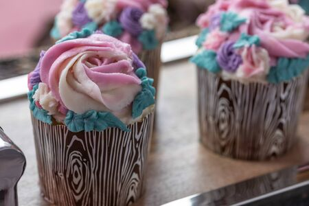 Close up Floral cupcakes on wood background Imagens