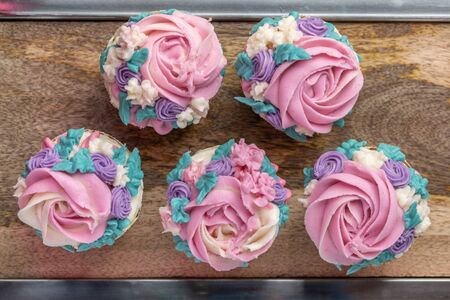 Top down Floral cupcakes on wood background