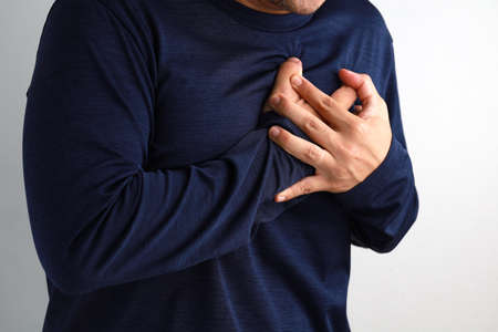 Close up a man with heart attack or heart burn condition, health and medicine concept.