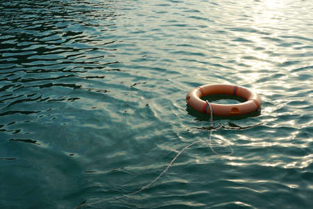 Orange color lifeguard Ring Buoy floating on seawater