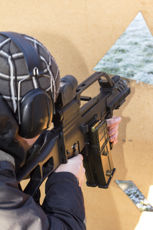 shooter aiming a rifle at a target