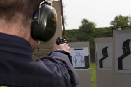 hombre disparando: Formación de los disparos de la policía en un campo de tiro Foto de archivo