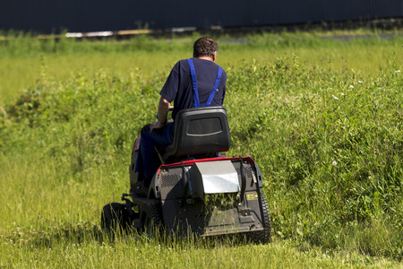 mows: worker mows the lawn tractor