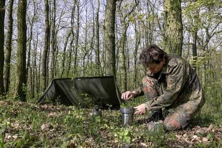 A man in a forest with a shelter cooks food