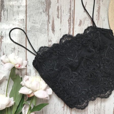 Black lace top on a wooden background Imagens