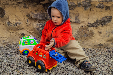 brooding: brooding boy playing his toy in the backyard, sitting on the gravel