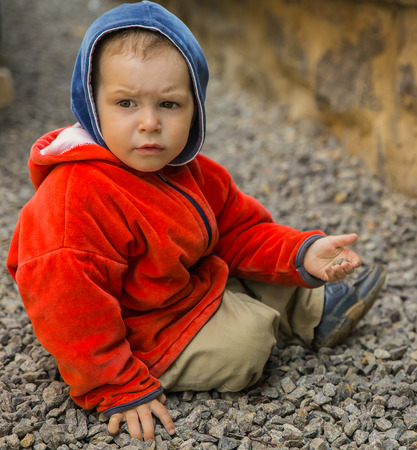 brooding: brooding boy playing his toy in the backyard,sitting on the gravel Stock Photo