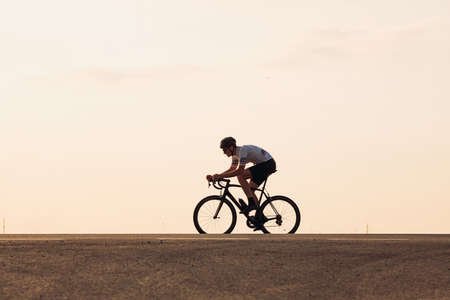 Muscular athlete in helmet cycling on asphalt road Banque d'images