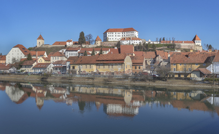 Old town Ptuj with mighty medieval castle on the hill and reflections in river Drava, Slovenia