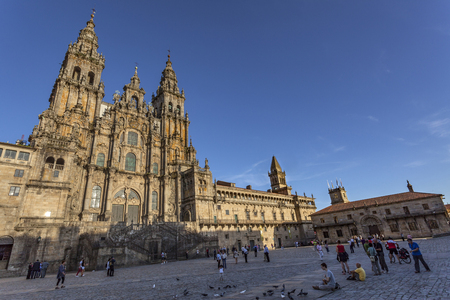 Obradoiro square with magnificent church of St. James and pilgrims in foreground in Santiago de Comostela,
