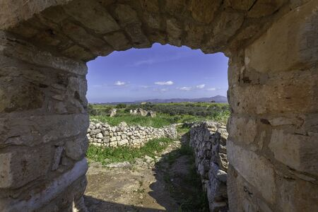 View through the massive door to ruins of ancient Aptera, Crete, Greece 免版税图像