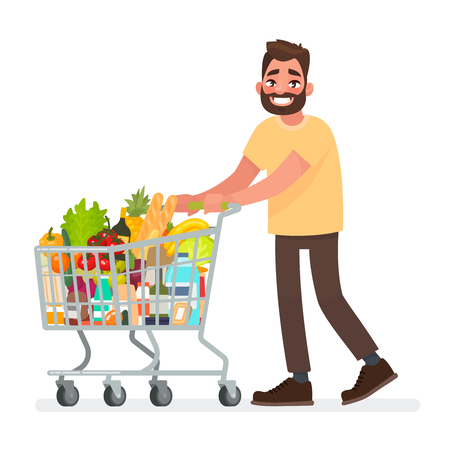 Man is carrying a grocery cart full of groceries in the supermarket.