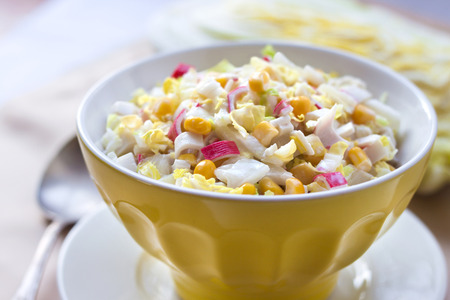Chinese cabbage, sweet corn and surimi salad in a yellow bowl Stock Photo