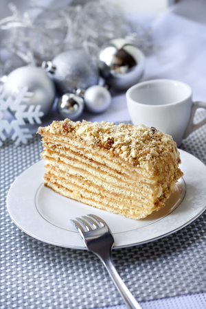 Piece of layer cake with custard and walnuts on a plate with Christmas balls on the background Stock Photo