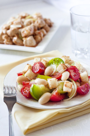 Salad with three kinds of tomatoes, boiled white kidney beans and croutons from white bread, with turkey stew on background