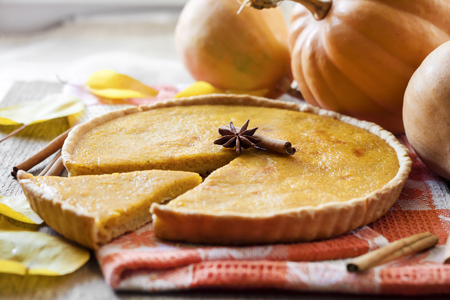 Homemade spicy pumpkin pie with cinnamon on a table with pumkings at background Stockfoto