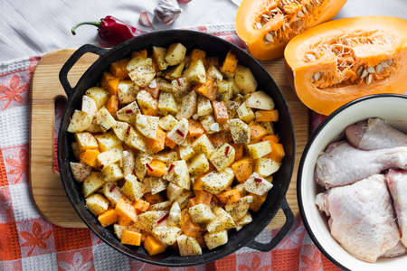 Cooking one-pot meal - chicken thighs and legs with potatoes and pumpkin baked in cast-iron pan