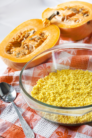 Raw washed millet in a glass pan in the process of cooking sweet milk porridge with pumpkin and raisins Stock Photo