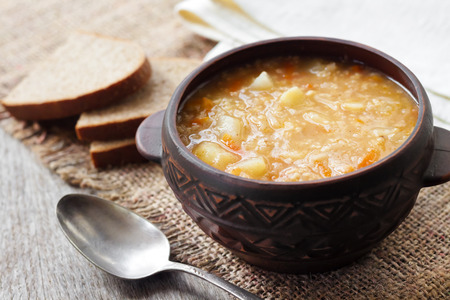 Kapustnyak - traditional ukrainian winter soup with sauerkraut, millet and meat in rustic bowl