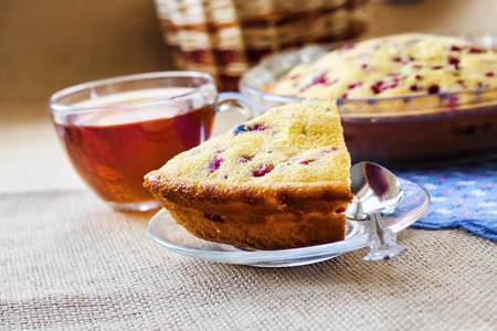Piece of cowberry pie on glass plate and cup of tea