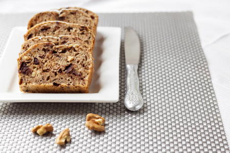 Banana cake with walnuts and dark chocolate on a white square plate