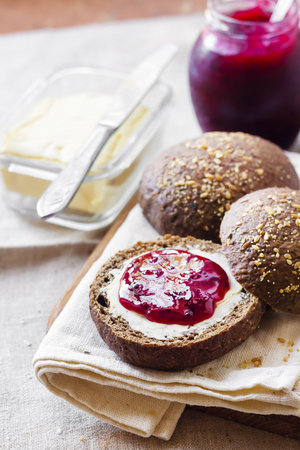 Homemade rye buns with linseeds, sesame and white poppy seeds served with butter and Jostaberry jam on wooden board Stockfoto