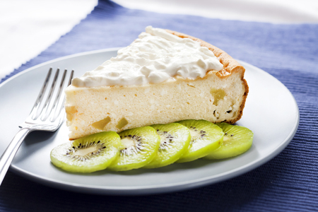 Homemade cottage cheese and semolina cake with kiwi fruit and cream on a plate