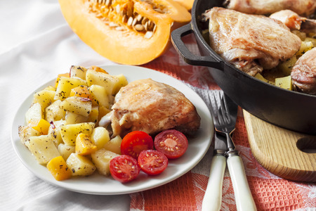 One-pot meal - chicken thighs and legs with potatoes and pumpkin baked in cast-iron pan Stock Photo