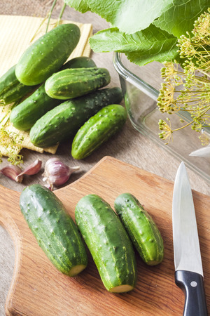 Fresh cucumbers on wooden board prepared for pickling in glass container