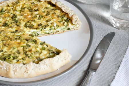 Tart with eggs and green onions on a plate with jar of water and glass on background