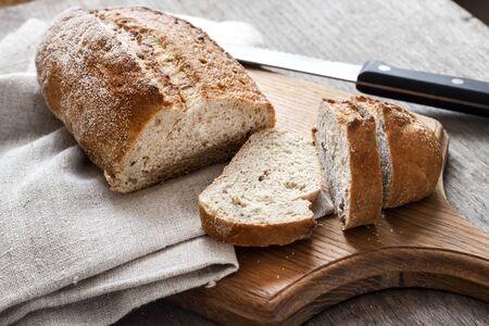 Brood van volkoren brood met plakjes op een houten bord op de keukentafel