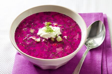 Holodnik - traditional Lithuanian (Russian, Ukrainian, Belorussian, Polish) cold beetroot soup with cucumber, boiled eggs and greens in white bowl on purple cloth Stock fotó