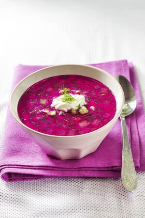 Holodnik - traditional Lithuanian (Russian, Ukrainian, Belorussian, Polish) cold beetroot soup with cucumber, boiled eggs and greens in white bowl on purple cloth Zdjęcie Seryjne