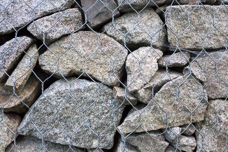 Gabion muur close-up. Gestructureerde achtergrond. Gabion is stenen in gaas die worden gebruikt voor erosiebestrijding en hellingsversterking